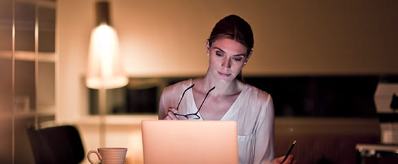 Kvinna sitter i ljuset av en laptop