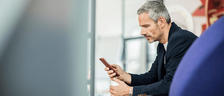 affärsman sitter ner och använder smartphone på kontoret