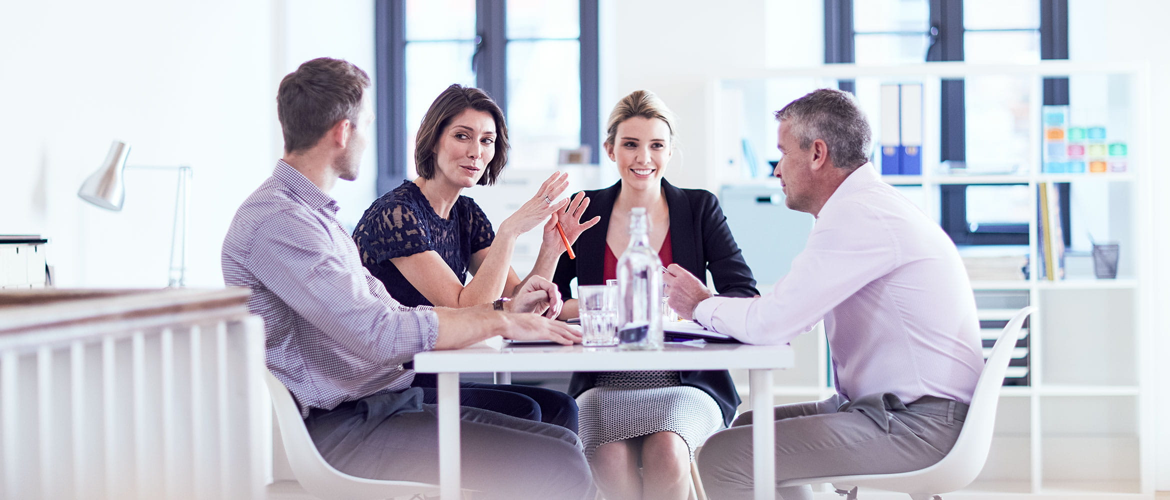 Four colleagues talking and smiling in an office setting