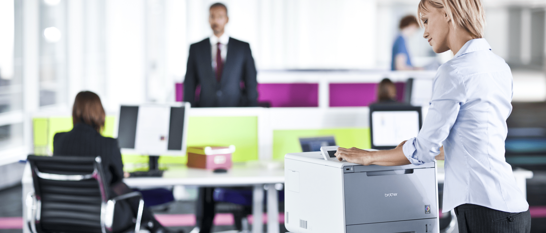 Upptaget kontor med kvinna som loggar in med pekskärm på en HL-L9200CDWT färglaserskrivare