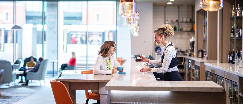 Female bar staff service female sat on bar stool, bottles, lights, chairs, cups