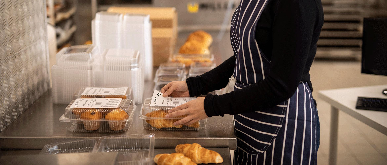 Arbetare märker förpackade croissanter och muffins i ett kök
