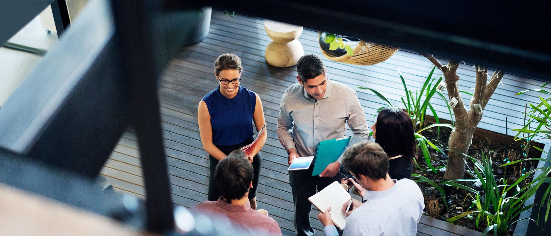 Fem anställda (två kvinnliga och tre manliga) på framtidens arbetsplats håller ett informellt affärsmöte ståendes på kontoret. Fotograferade ovanifrån. Medarbetarna håller filer, anteckningar och surfplattor när de samarbetar.