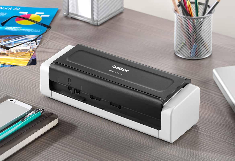 En vit kompakt skanner står på ett skrivbord