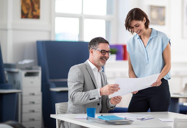 En man och kvinna läser på ett papper på ett kontor med en skrivare i bakgrunden.