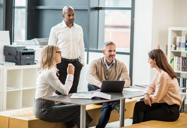En grupp människor på ett kontor med monolaserskrivare i bakgrunden