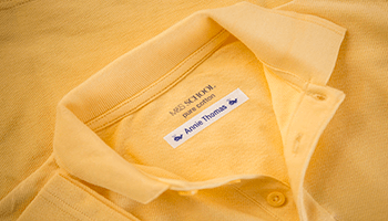 Yellow school polo shirt with a name label