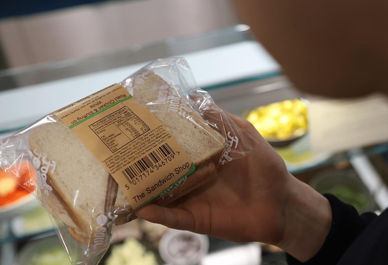 Person håller en smörgås i klar plastpåse med brun etikett med ingredienser