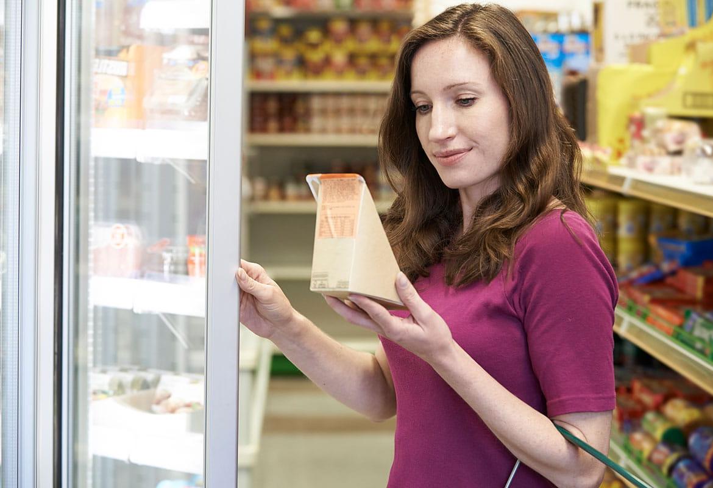 Kvinna i vinröd tröja läser på smörgås vid kyl