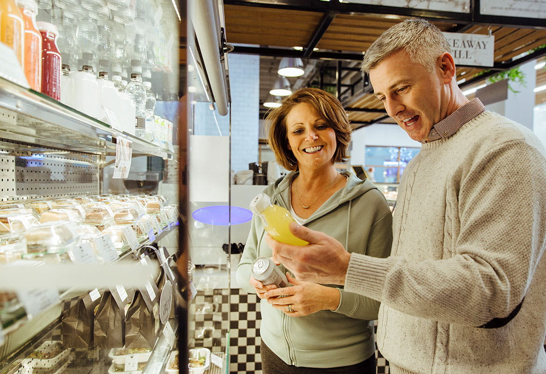 Kvinna och man vid kyl jämför flaskor med dryck