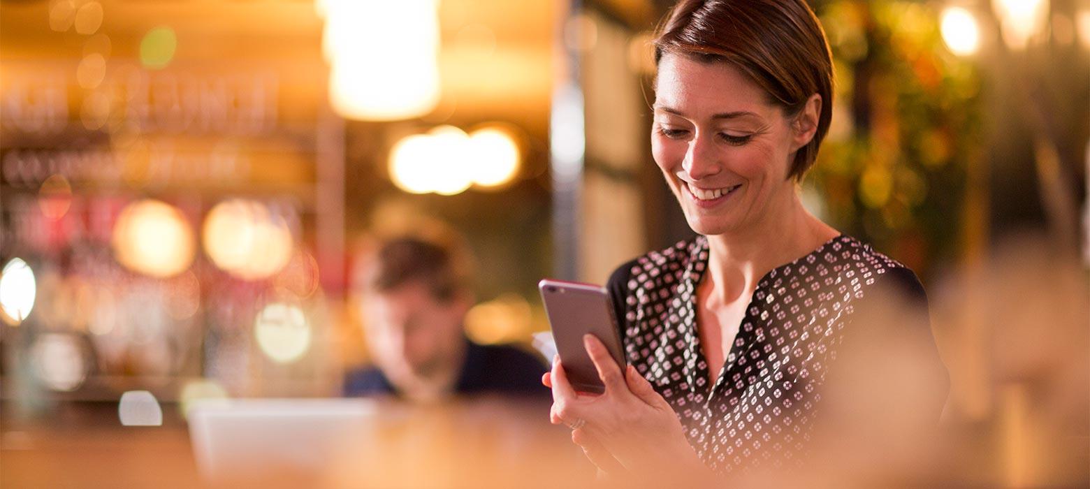 Kvinna kollar nyheter på sin iphone