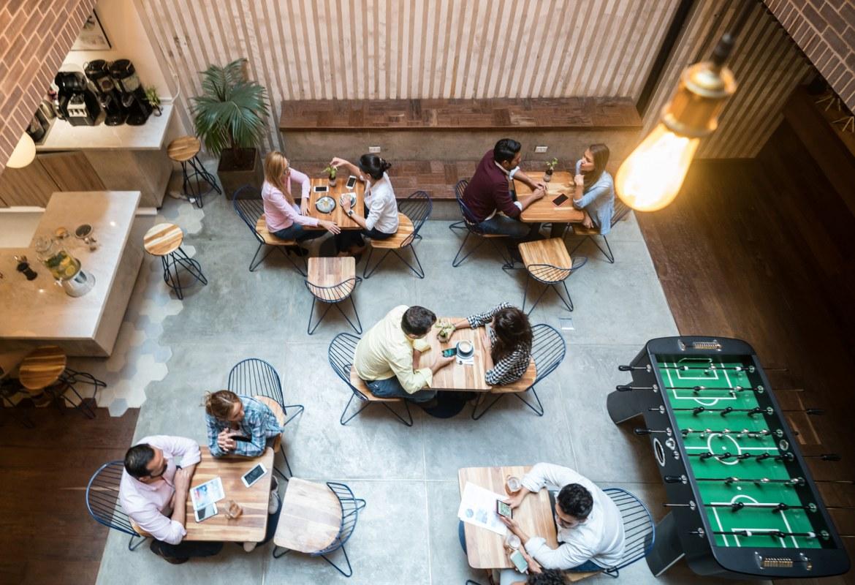 Framtidens arbetsplats ses från en hög vinkel och tittar ner på ett snyggt, minimalistiskt kontor med bord och ett spelbord