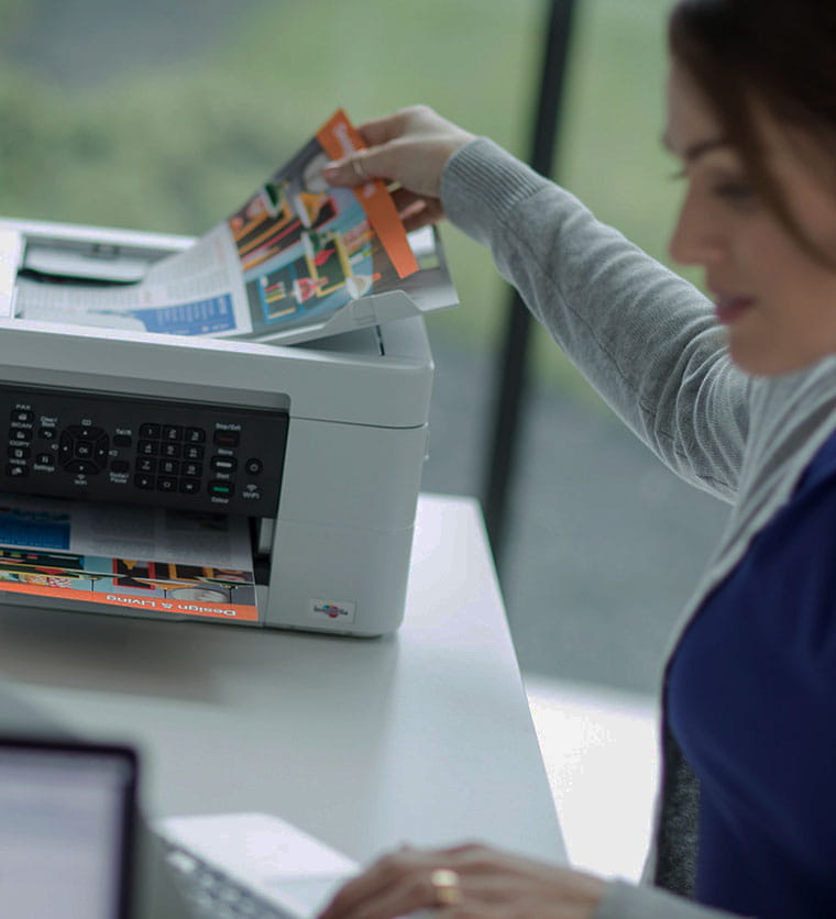 Woman sat at desk picking up document from printer