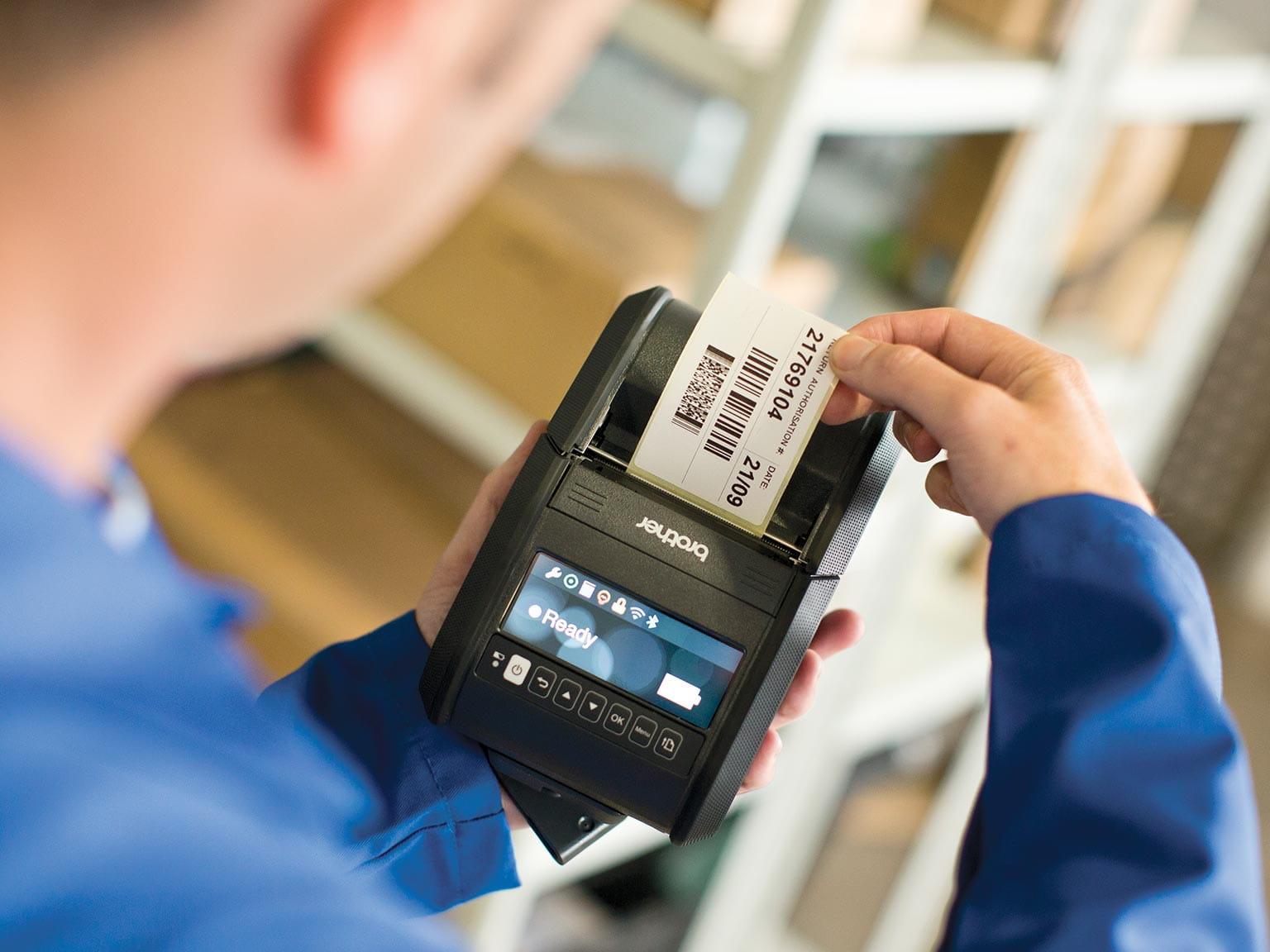 Varastotyöntekijä poimii viivakooditulostetta RJ-mobiilitulostimesta