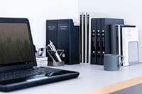 Bärbar dator på skrivbord med mappar bredvid