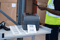 TD-4T label printer on metal trolley with scanner printing labels