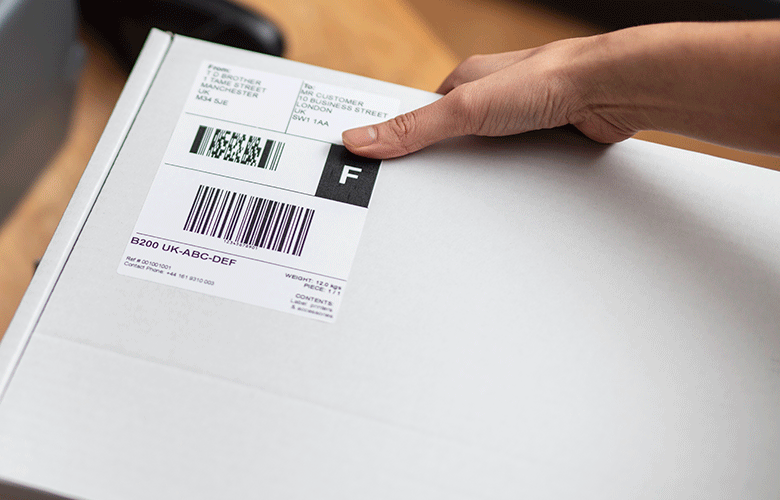 White shipping label being placed on white box by hand