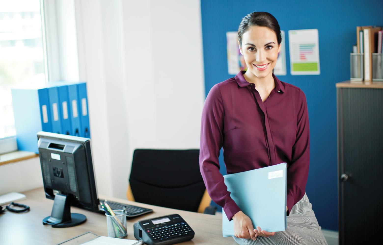 Kvinna på ett kontor med Brother P-touch märkta mappar