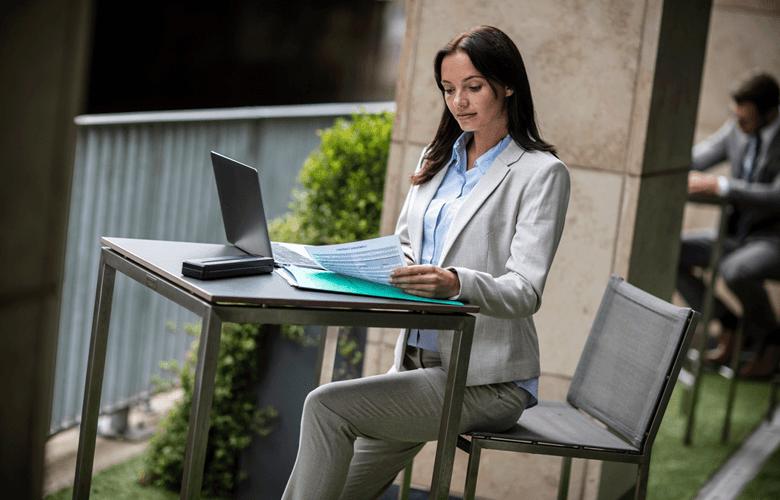 Kvinna jobbar med mobil skrivare på café