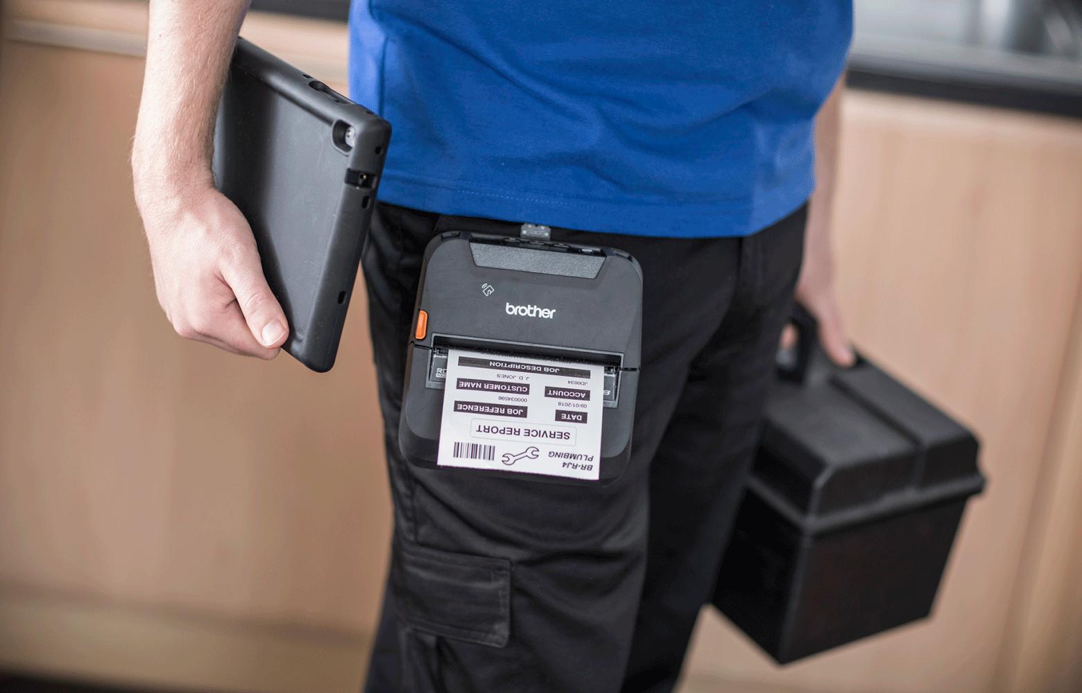 Servicepersonal på fältet med mobil skrivare i bältet