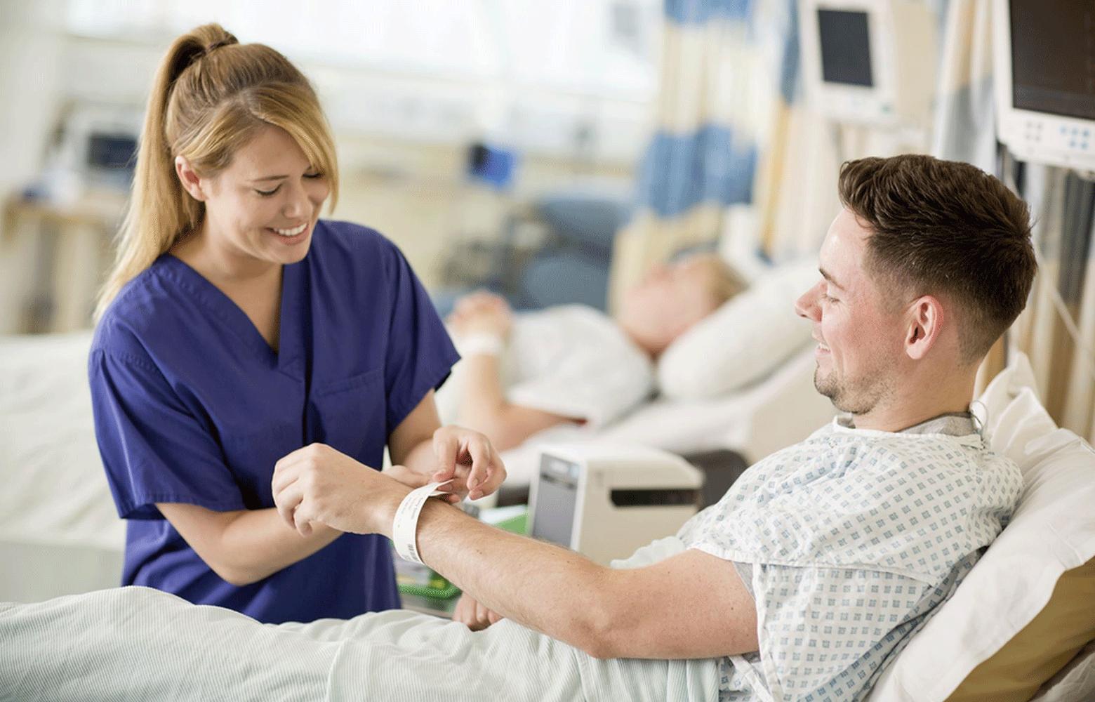 Sjuksköterska sätter på id-armband från Brother på patient