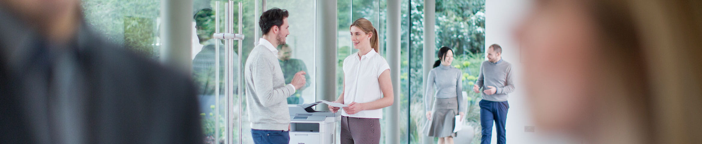 Man and woman talking next to a printer